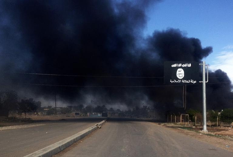 Smoke billows behind an Islamic State group sign during clashes between militants from the Islamic State group and Iraqi security forces during a military operation to regain control of the town of Sadiyah, 60 miles (95 kilometers) north of Baghdad, Iraq in Diyala province, Iraq. Iraqi authorities say Iraqi troops backed by Shiite militias have retaken two towns seized previously by militants in an eastern province. (AP Photo)