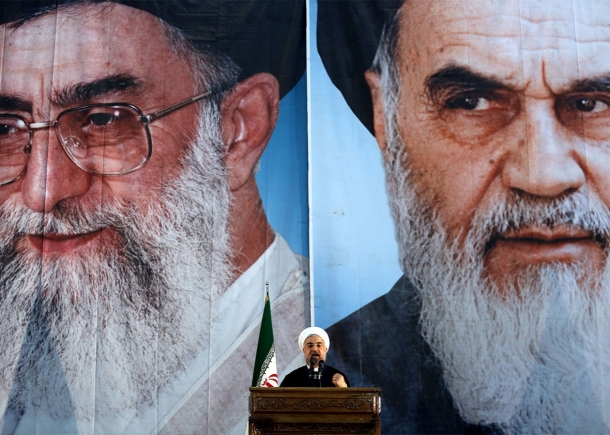 Iranian President Hassan Rouhani delivers a speech under portraits of Iran's Supreme Leader Ayatollah Ali Khamenei, left, and the founder of the Islamic Republic, Ayatollah Ruhollah Khomeini, right, in a suburb of Tehran on June 3, 2014.